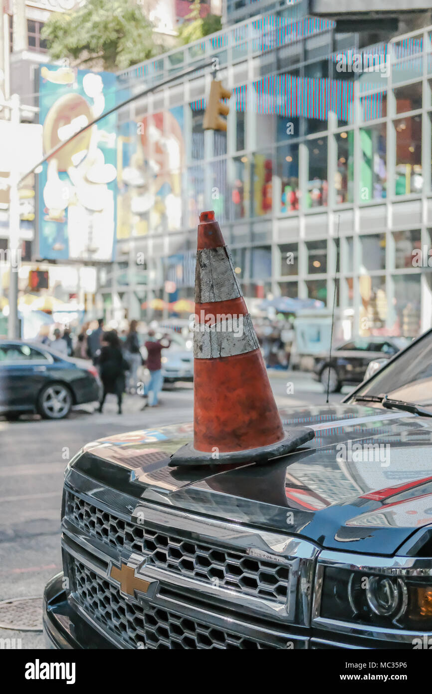 Single traffic cone seen illegally placed on a bonnet of an SUV vehicle which has been parked in a No Parking zone in central Manhattan. - Stock Image