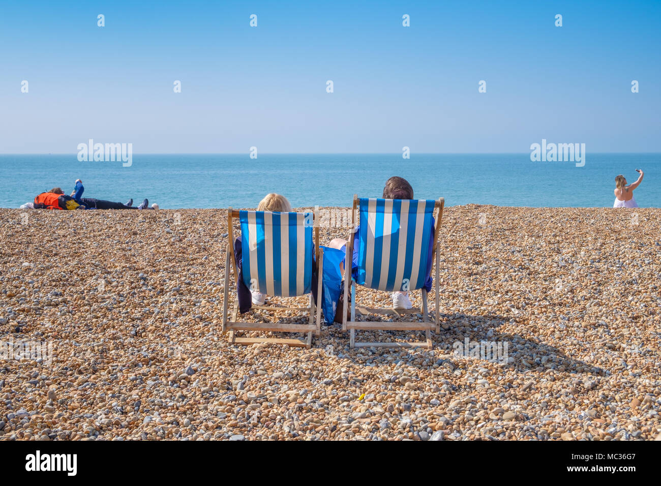 BRIGHTON, UK - APRIL 8, 2017: Couple sitting in deckchairs on a sunny April day on Brighton beach in April 2017. Stock Photo
