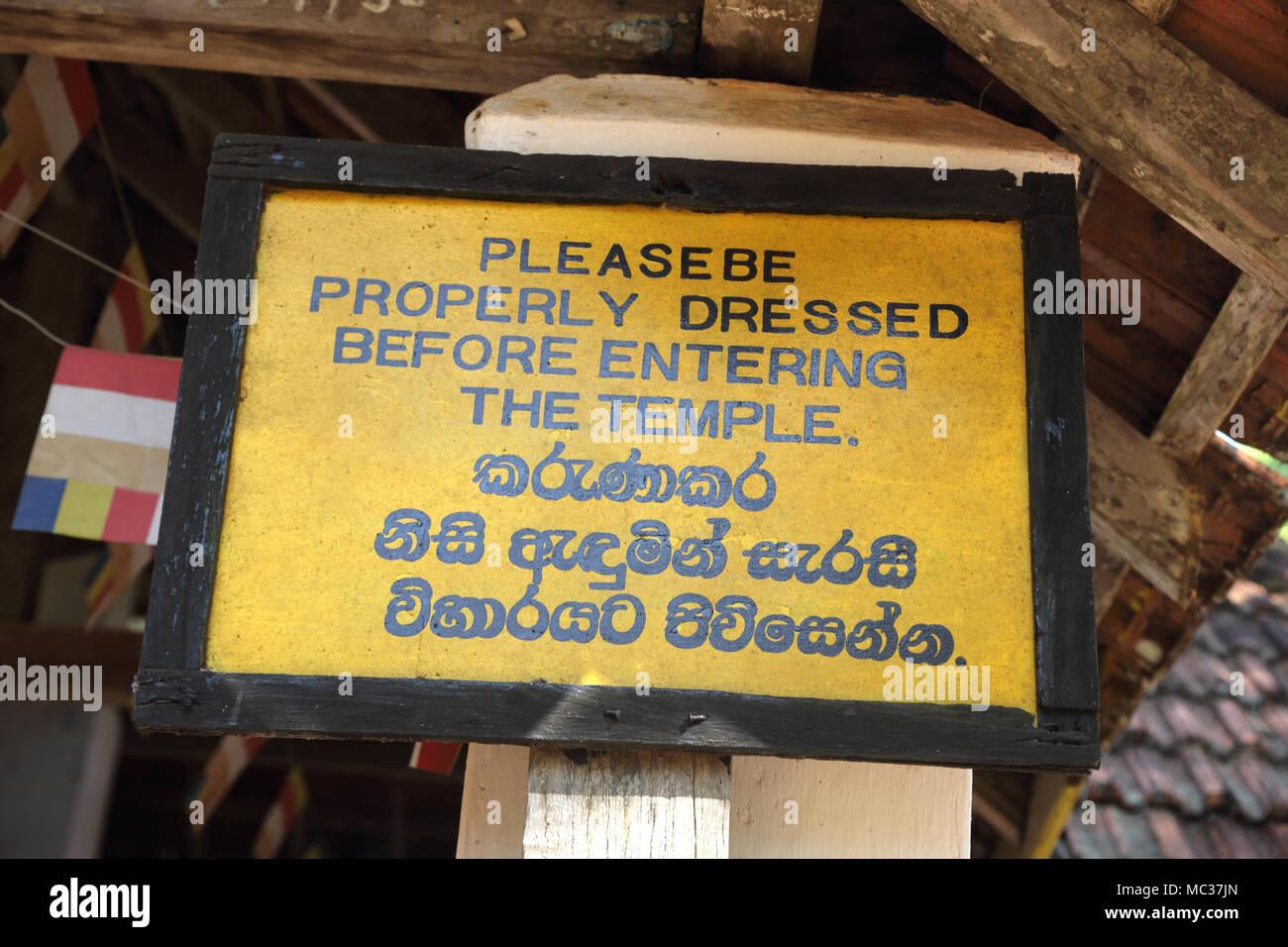 "Avukana Ancient Rock Temple Kekirawa North Central Province Sri Lanka Bilingual Sign "" Please be properly dressed before entering the temple"" Stock Photo"