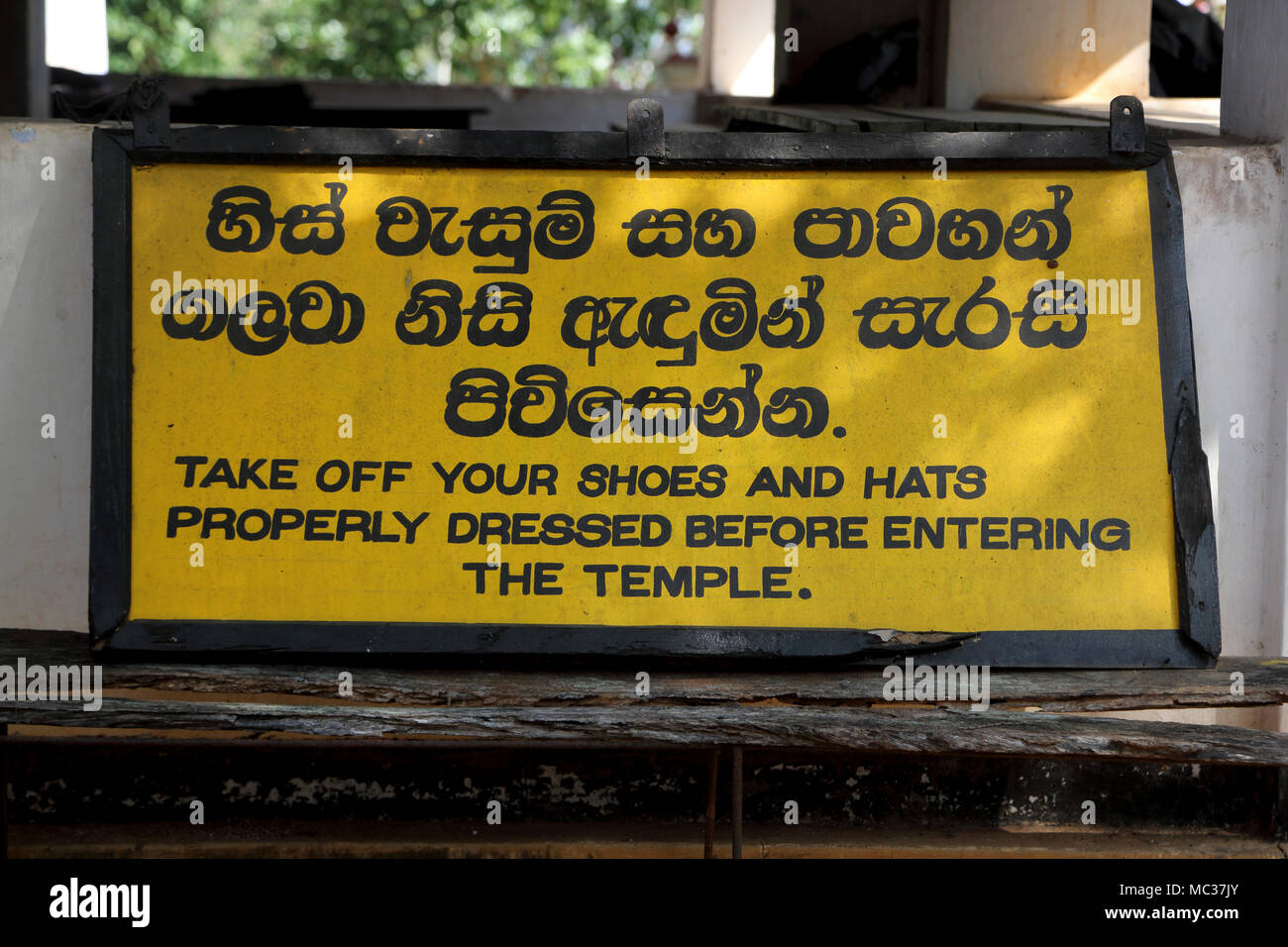 """Avukana Ancient Rock Temple Kekirawa North Central Province Sri Lanka Bilingual Sign """" Take off shoes and hats properly dressed before entering the te Stock Photo"""