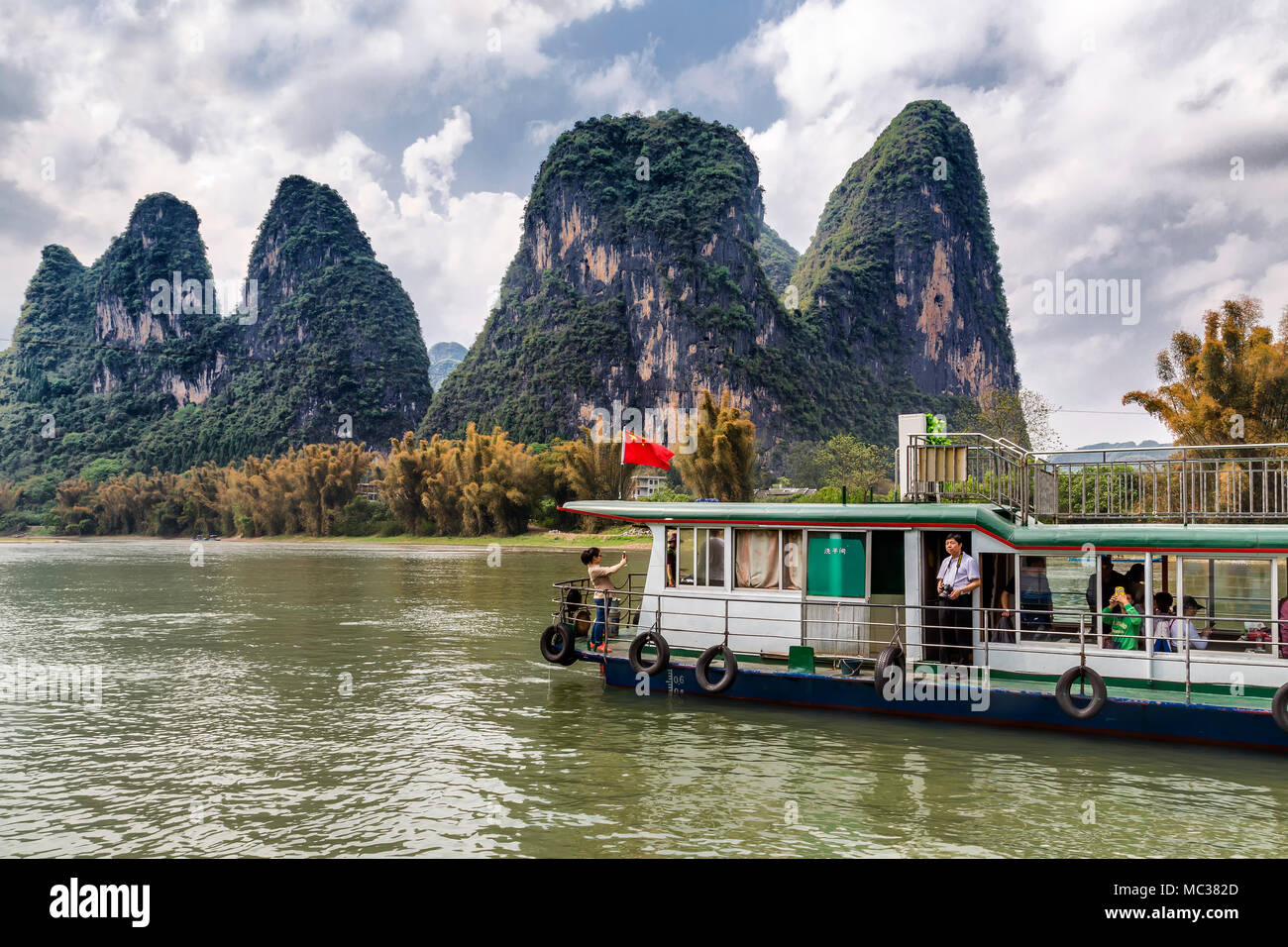 A tourist boat carries passengers along the Li River, Yanshuo, China. They look out at the unusual formation of the karst mountains. - Stock Image