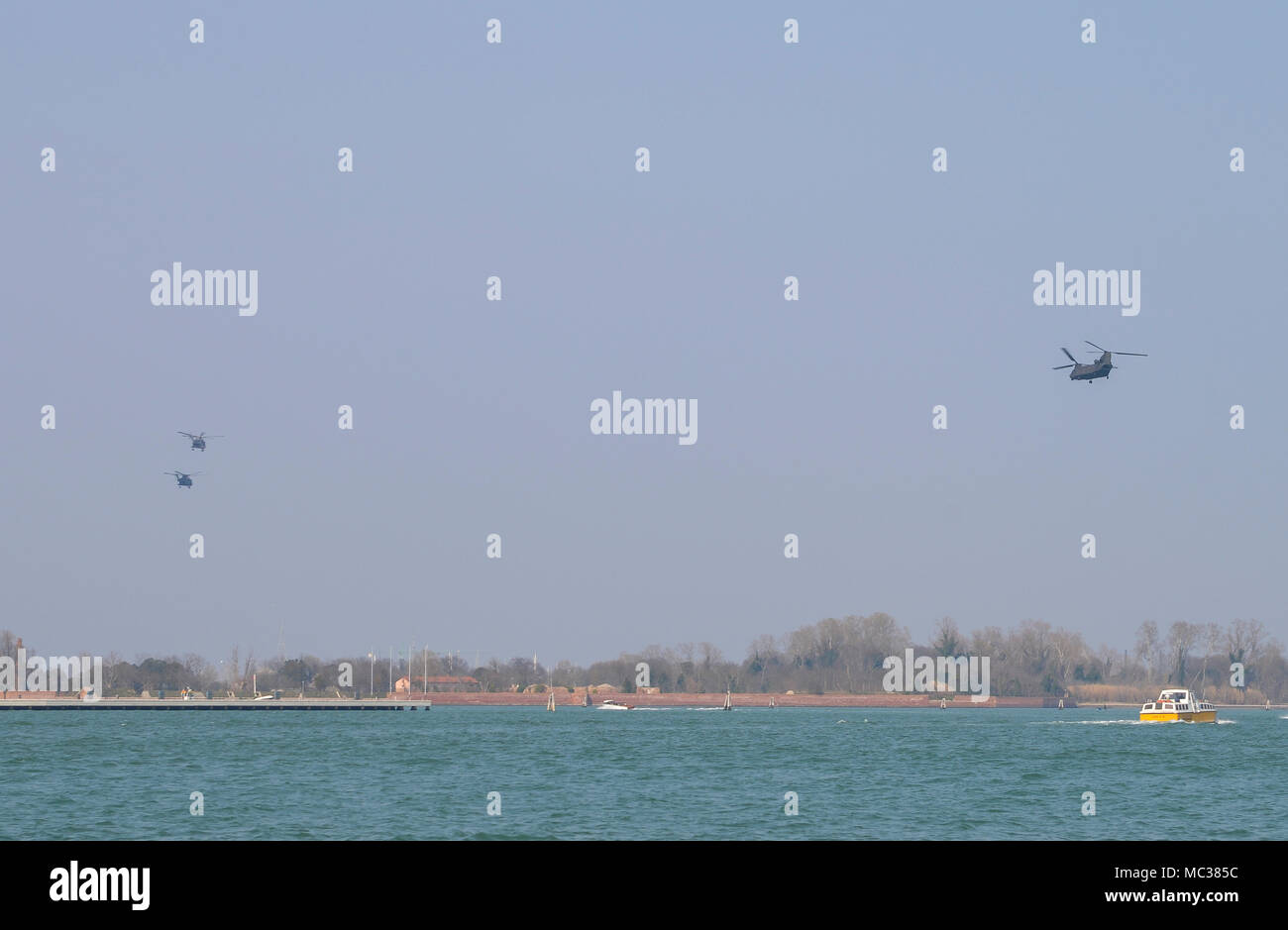 Military Helicopters in formation over the Venetian lagoon heading towards Aviano Air Base in Northeastern Italy. - Stock Image