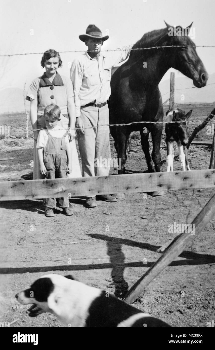 A farm family on the Great Plains of the US stands for a portrait behind some barbed wire, ca. 1935. - Stock Image