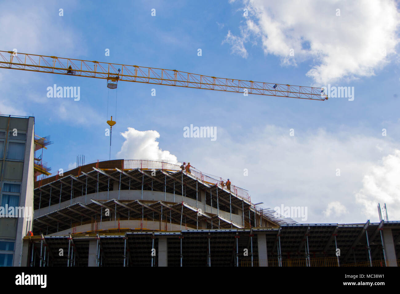 Crane and construction workers. Workers on multi-story building. - Stock Image