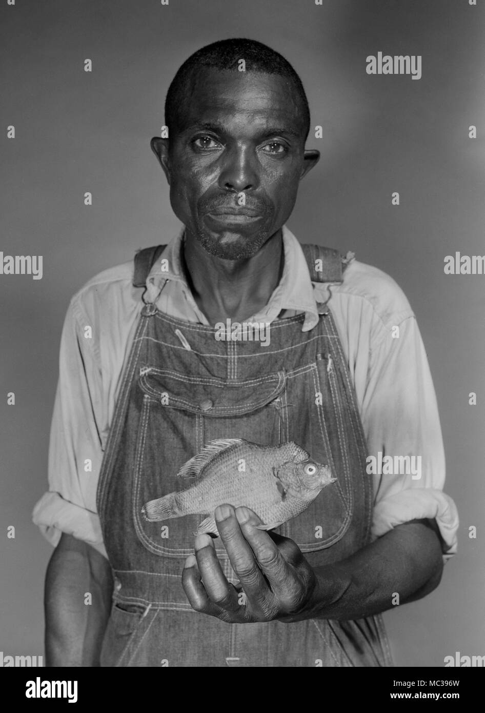 A man displays an odd looking fish he caught — possibly a longear sunfish — in Georgia, cal 1963. - Stock Image