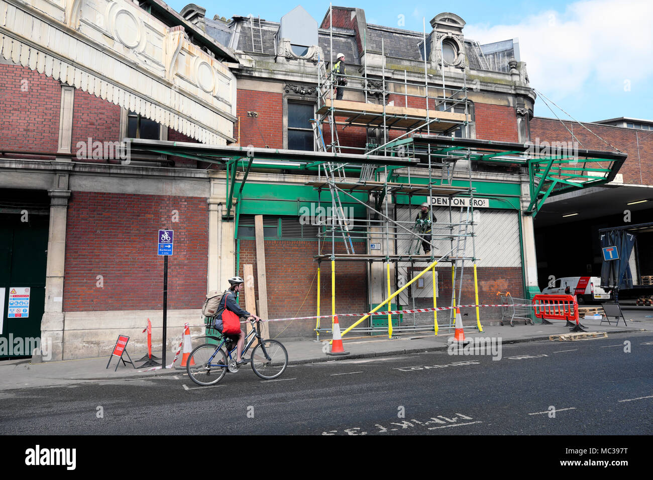 Cyclist cycling past men working on scaffold on old market building at West Smithfield, London UK   KATHY DEWITT - Stock Image