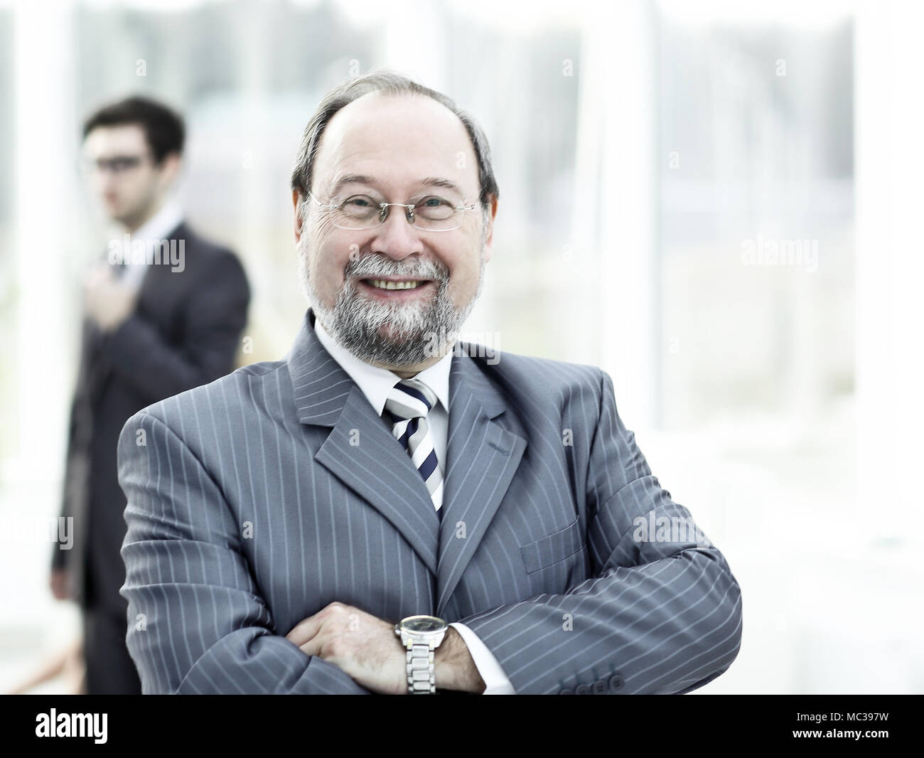 portrait of a senior businessman on blurred background office. - Stock Image