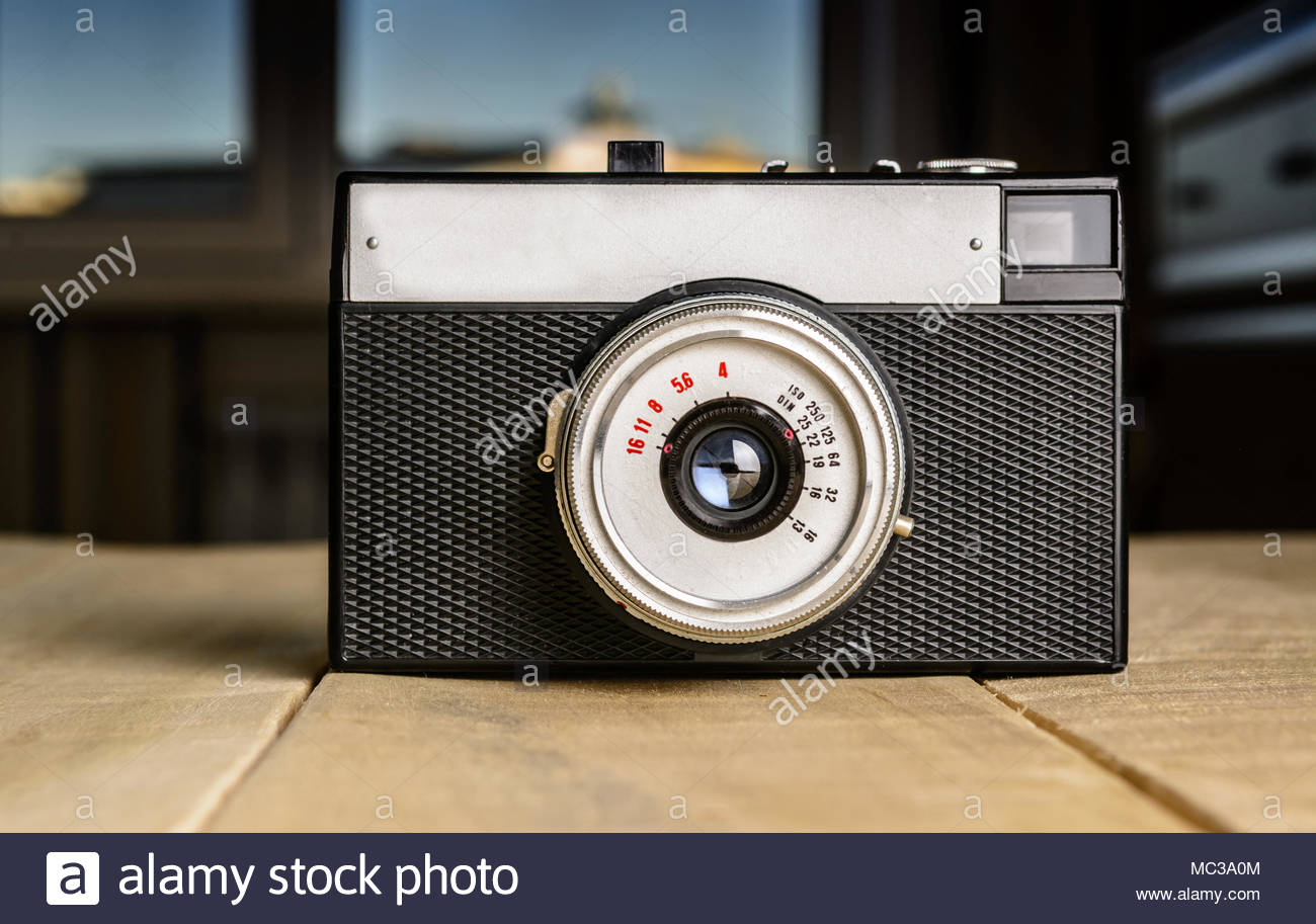 Old Soviet film camera stands on a wooden table - Stock Image