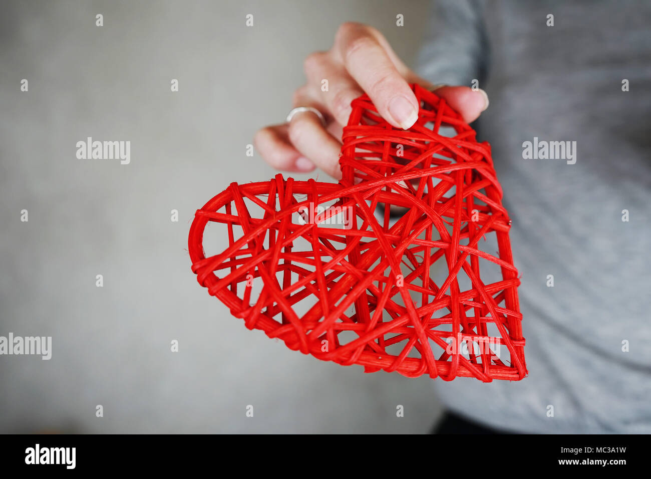 Young woman holding a red heart - Stock Image