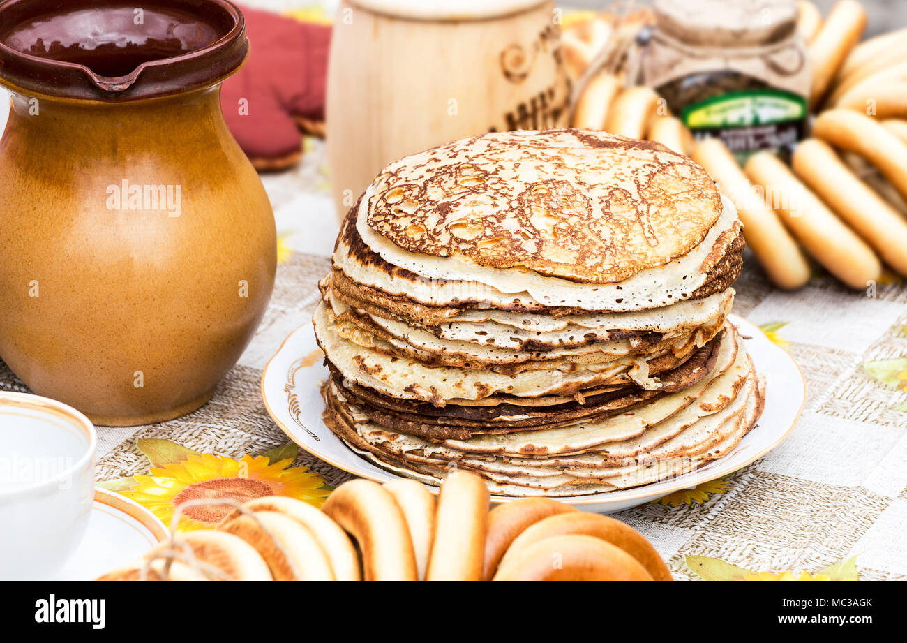 Stack of tasty fried pancakes and bagels on the table - Stock Image