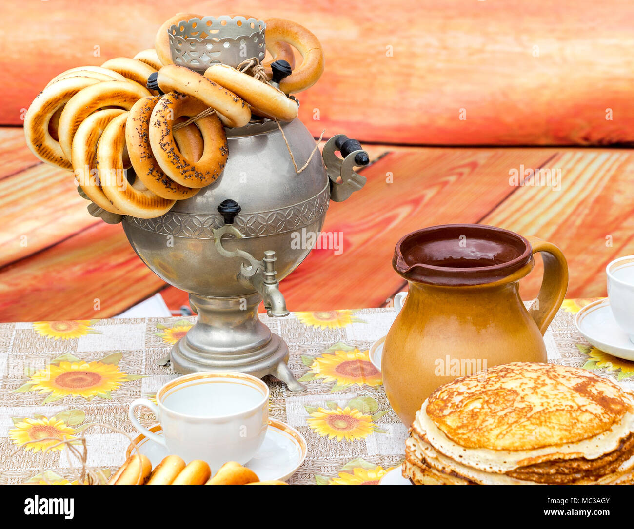 Traditional russian samovar with tasty bagels and ceramic tableware on the table & Traditional russian samovar with tasty bagels and ceramic tableware ...