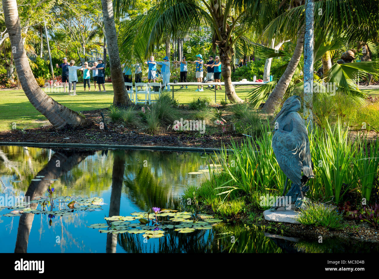 Tai Chi class on the lawn by a pond at Naples Botanical Gardens, Naples, Florida, USA - Stock Image