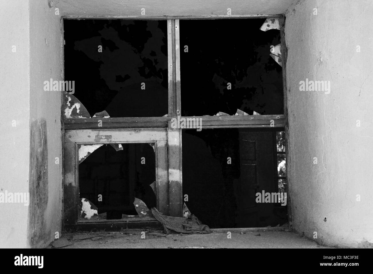 Shattered window in a run down, disused government building, Rhodes, Greece - Stock Image
