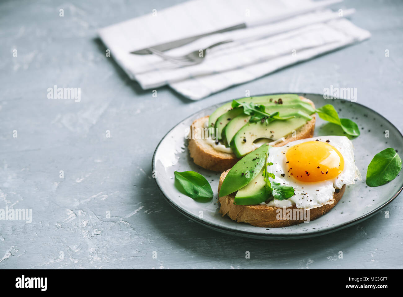 Avocado Sandwich with Fried Egg - sliced avocado and  egg on toasted bread with arugula for healthy breakfast or snack, copy space. - Stock Image