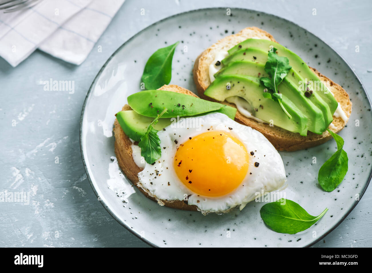 Avocado Sandwich with Fried Egg - sliced avocado and  egg on toasted bread with arugula for healthy breakfast or snack. - Stock Image