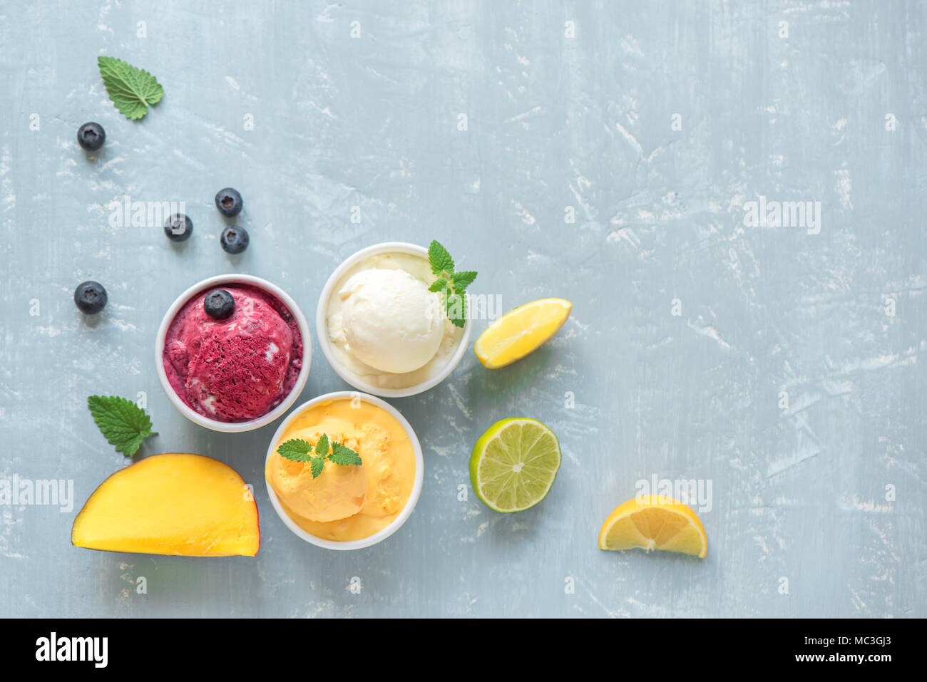 Three various fruit and berries ice creams on blue background, copy space. Frozen yogurt or ice cream with lemon, mango, blueberries - healthy summer  - Stock Image