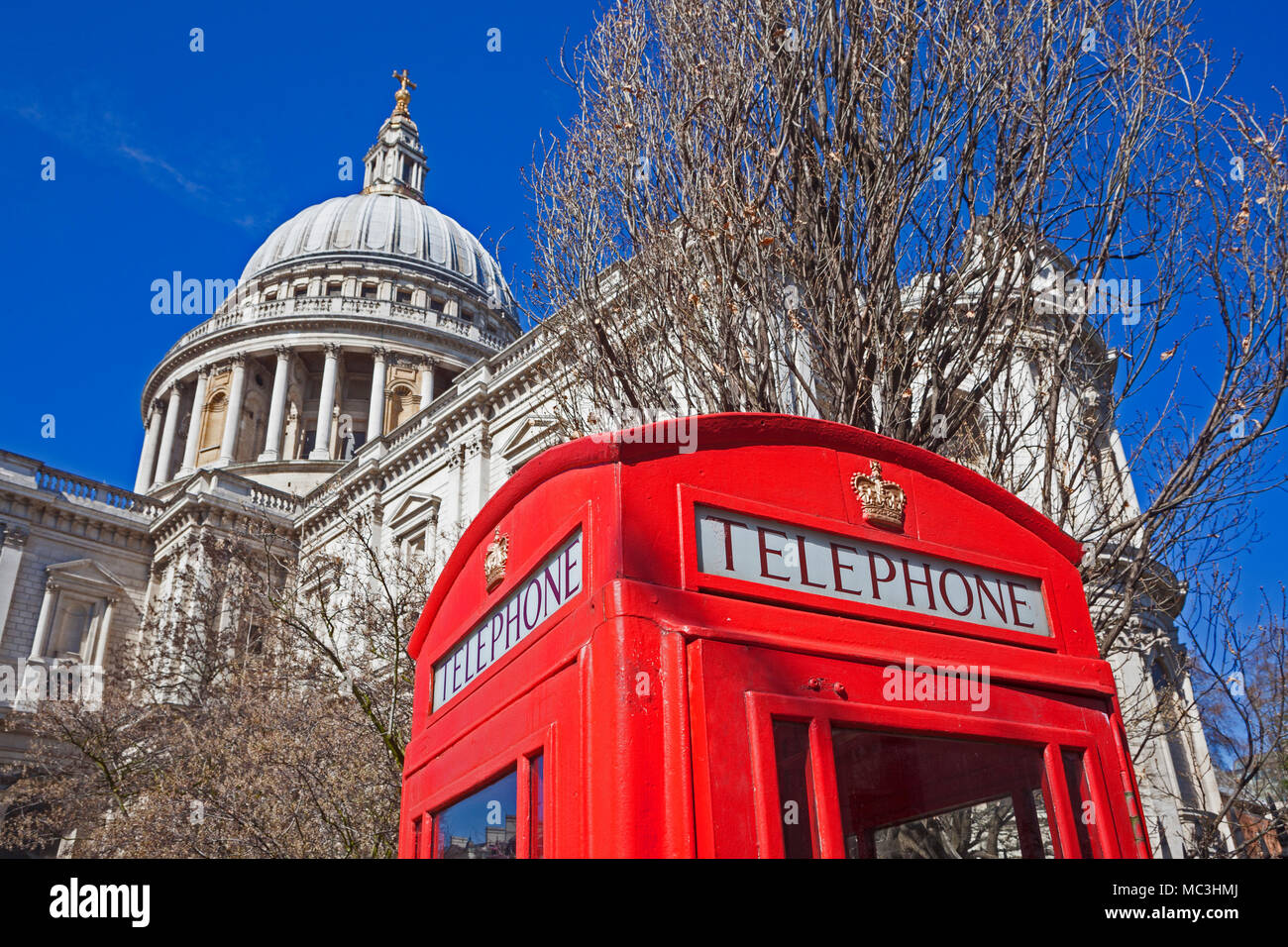 City of London   A traditional red telephone box in St Paul's Cathedral Gardens contrasting with the cathedral itself - Stock Image