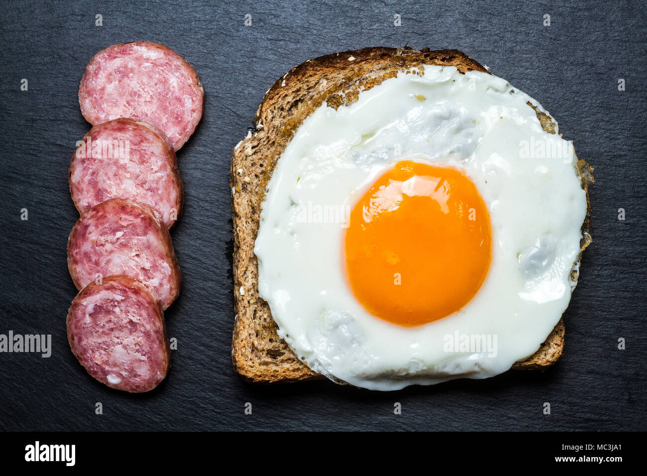 Fried egg on a toast and silced sausage. Florianopolis, Santa Catarina, Brazil. Stock Photo