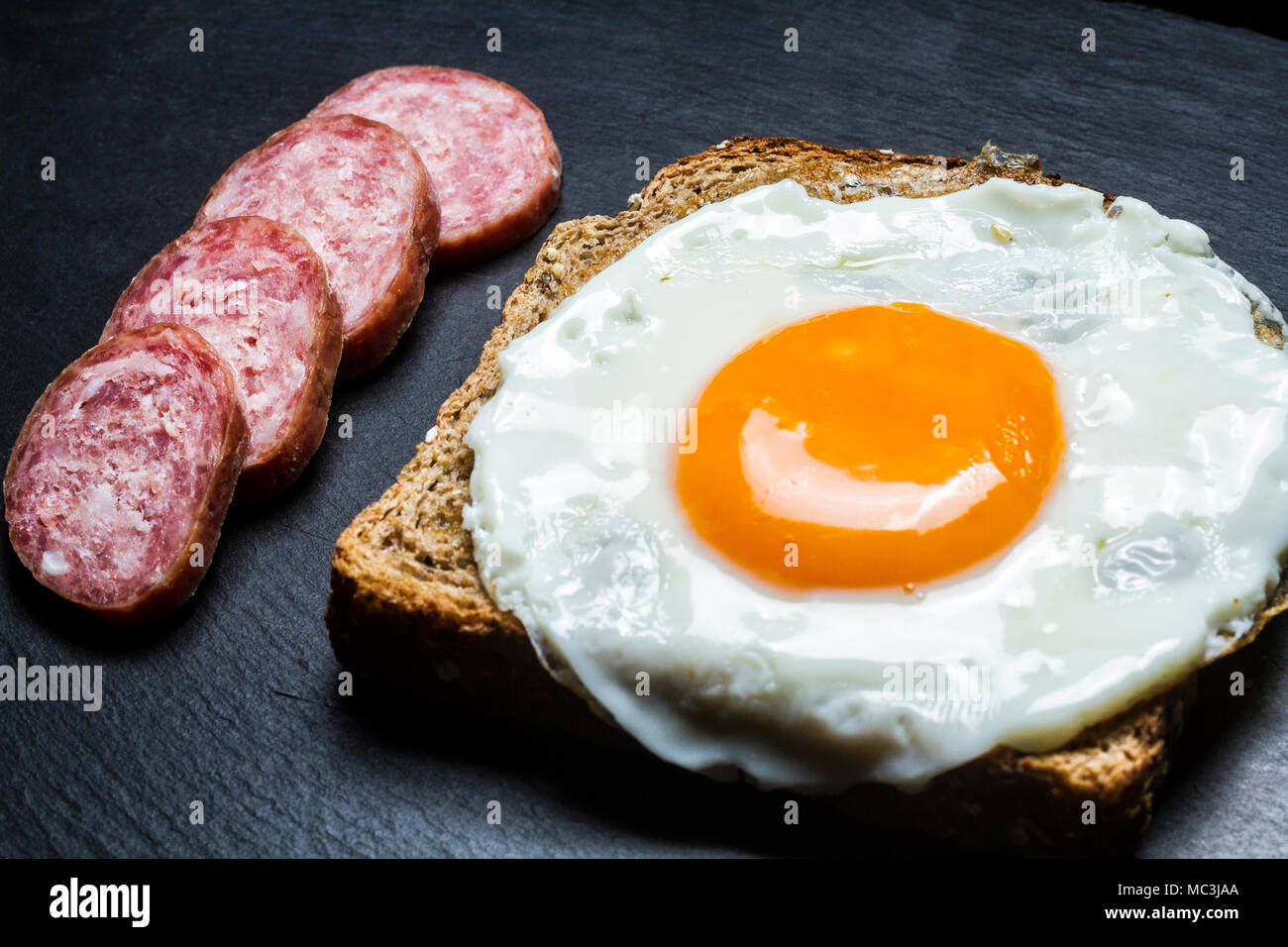 Fried egg on a toast and silced sausage. Florianopolis, Santa Catarina, Brazil. - Stock Image