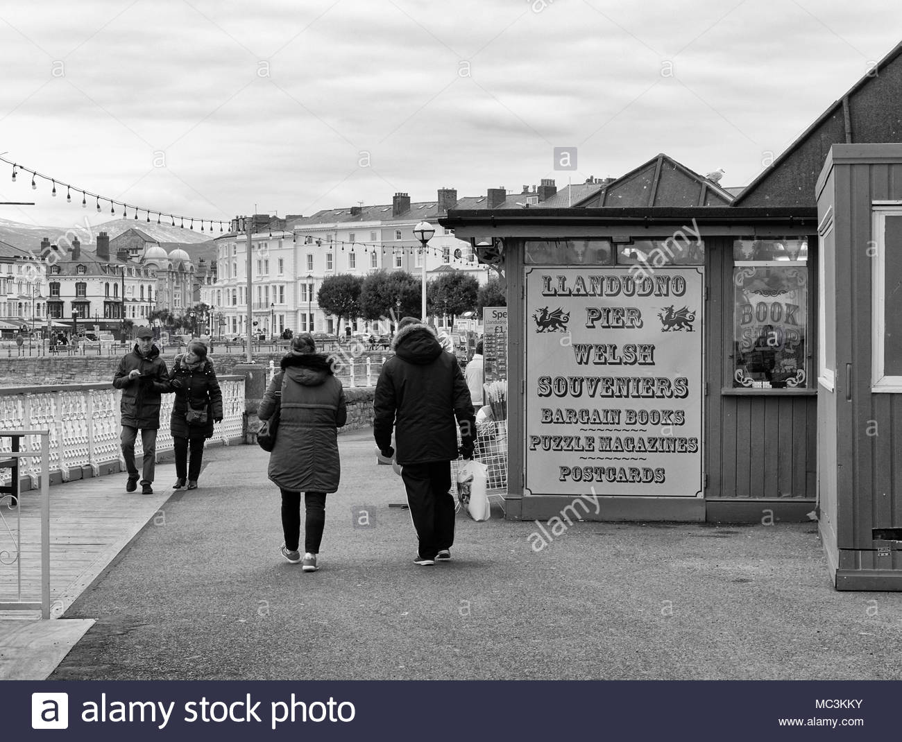 People walking on the promenade in the welsh seaside town of Llandudno in north wales uk - Stock Image