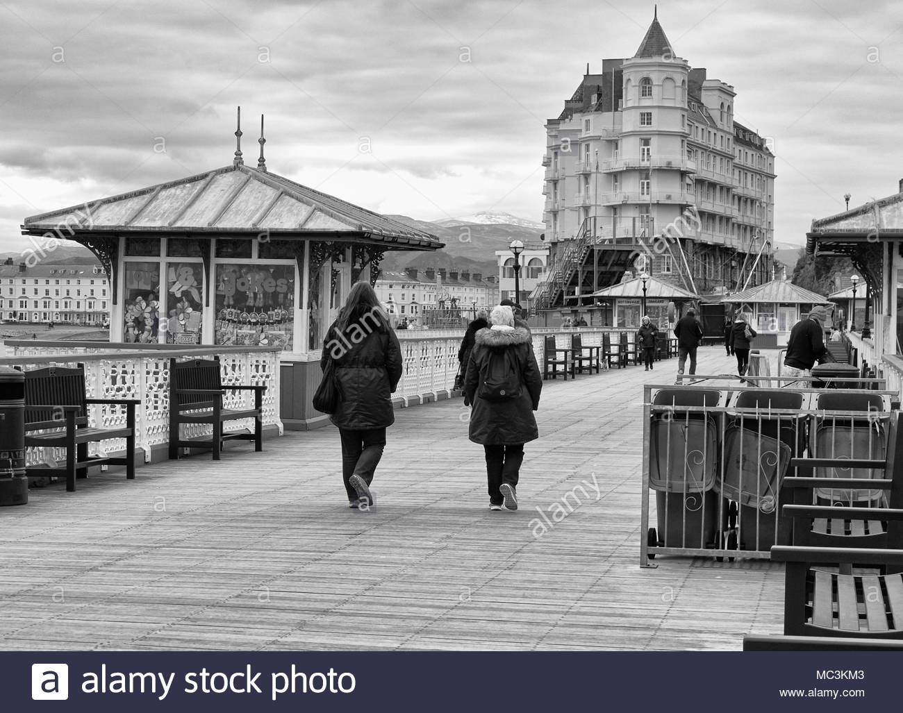 People walking on the pier in llandudno seaside town in north wales uk in the springtime - Stock Image