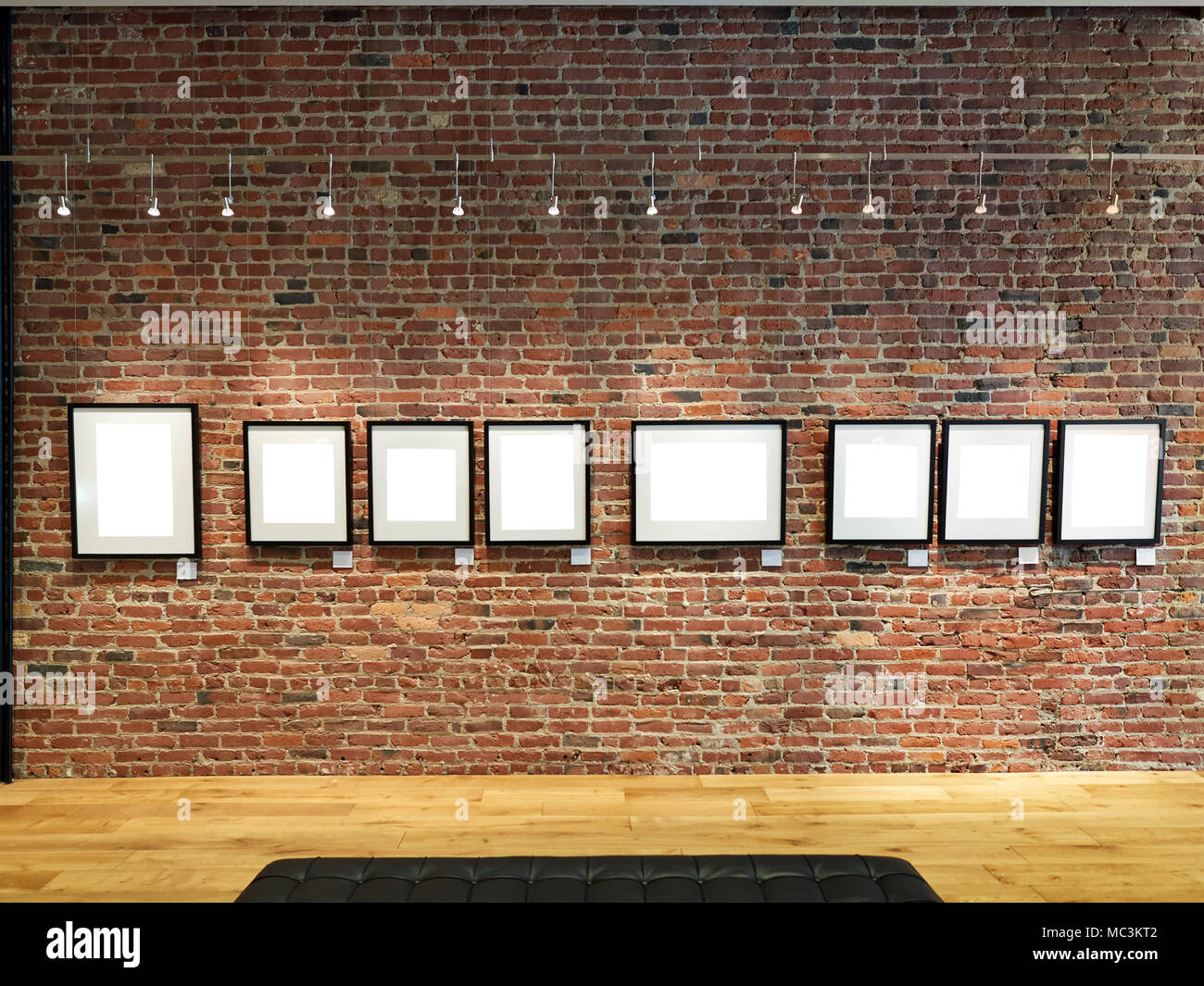 Clipping Path photo gallery frames empty on a brick wall - Stock Image