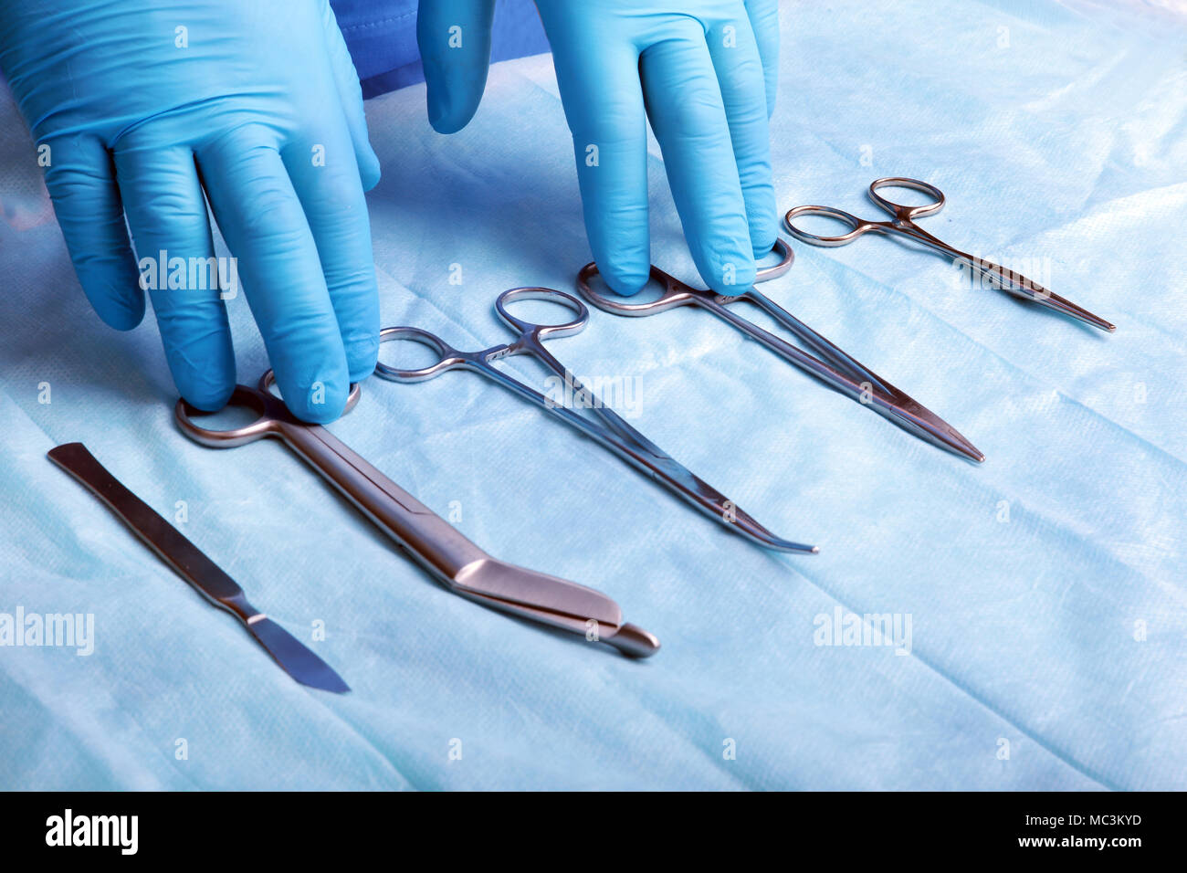 Detail shot of sterilized surgery instruments with a hand grabbing a tool , - Stock Image