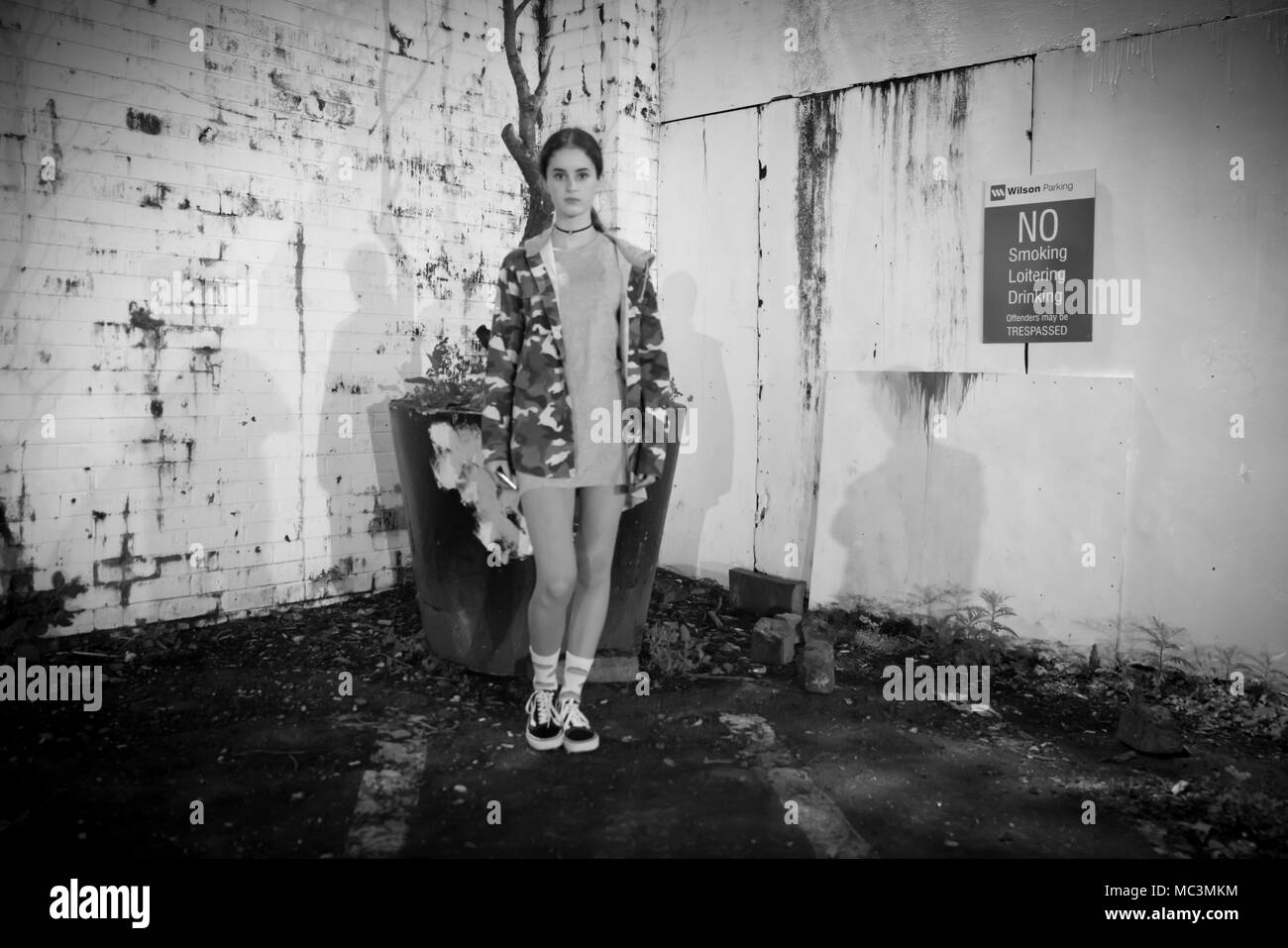 AUCKLAND, NEW ZEALAND - MARCH 25, 2018; Deadpan night scene grainy dark image girl  standing straight faced  in front grungy wall in monochrome with N - Stock Image