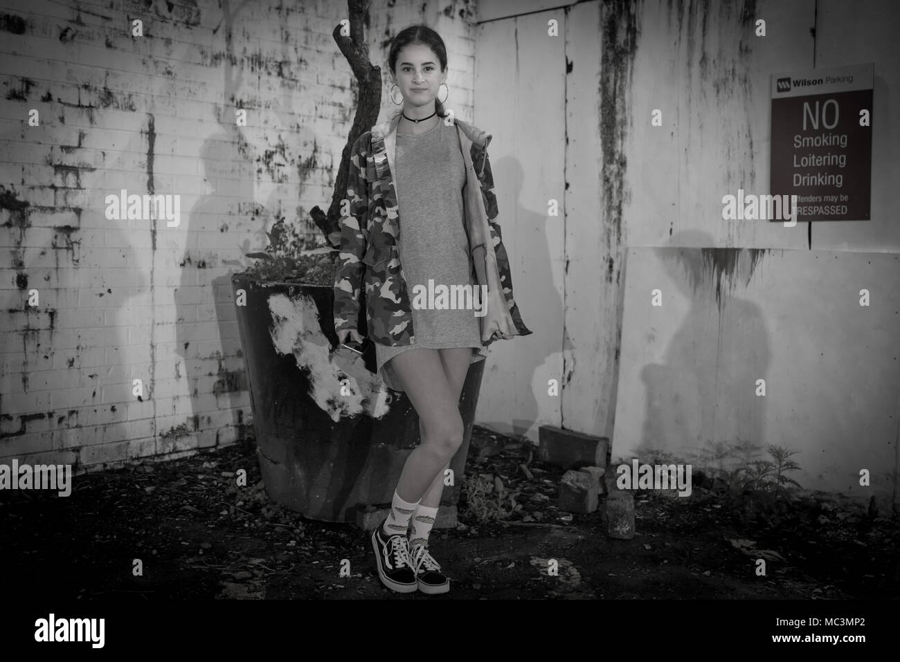 AUCKLAND, NEW ZEALAND - MARCH 25, 2018; Deadpan night scene Grainy dark image girl smiling standing in front grungy wall in monochrome with No loiteri - Stock Image