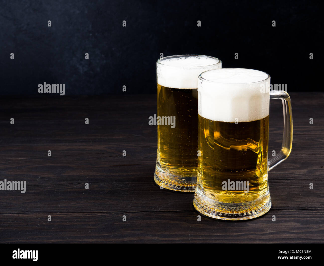 Two glasses of lager served on old wooden planks - Stock Image