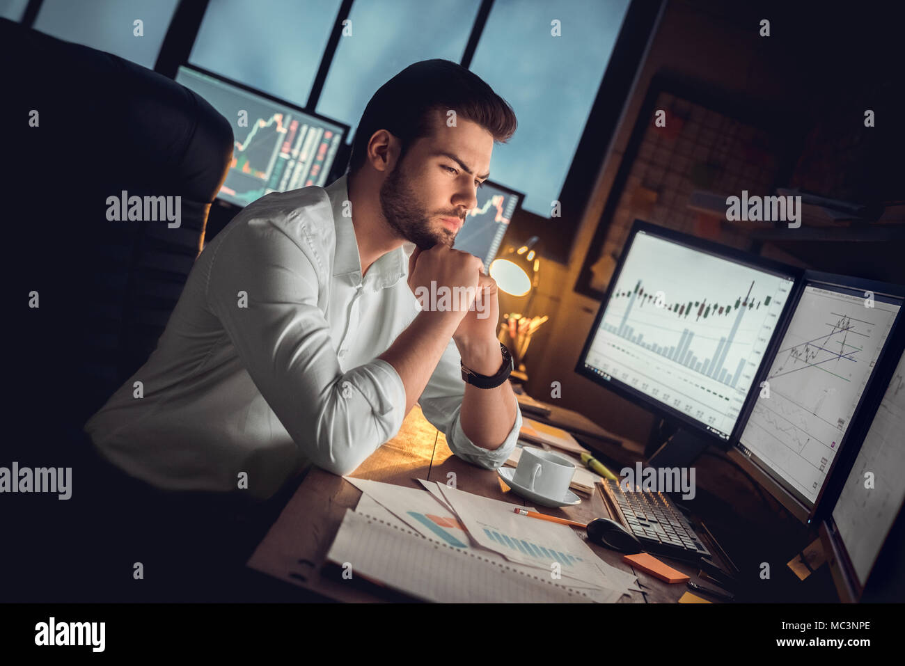Focused thoughtful trader or serious investor working at night overtime analyzing stock trading graphs looking at computer monitors controlling market - Stock Image