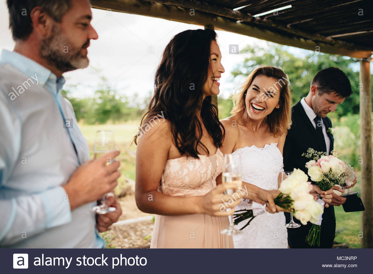 Happy Bridesmaid Giving Speech To Bride And Groom At Wedding