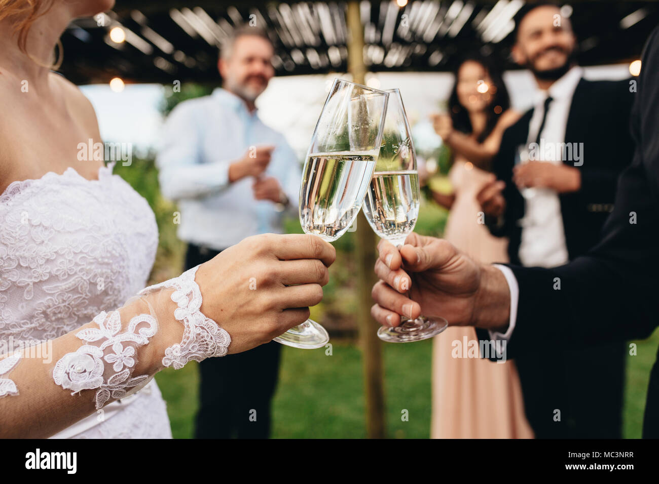 Close up of bride and groom toasting champagne glasses at wedding party. Newlyweds clinking glasses at wedding reception outside. - Stock Image