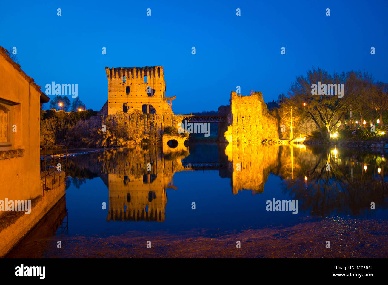 The ruins of Borghetto sul Mincio towers bridge on the river, with the pedestrial lane. Veneto region, Italy. Night view at blue hour. Stock Photo