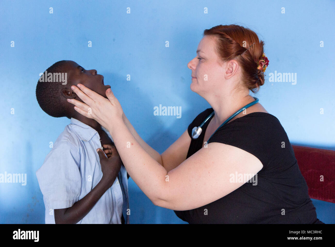 Uganda. June 13 2017. A white foreign missionary doctor examining a child patient at a primary school. Stock Photo