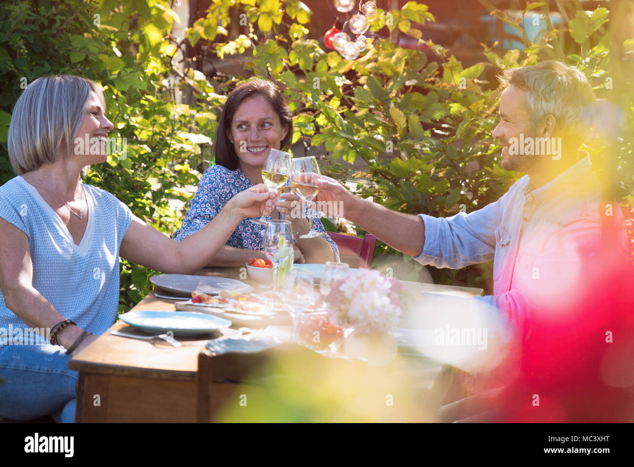 In summer, a group of friends in their forties gather around a table in the garden to share a good time around a meal. - Stock Image