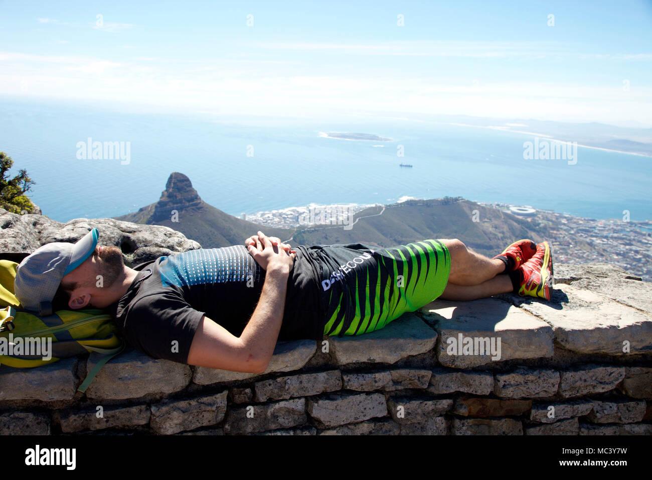 Tourist takes a siesta on summit of Table Mountain - Stock Image