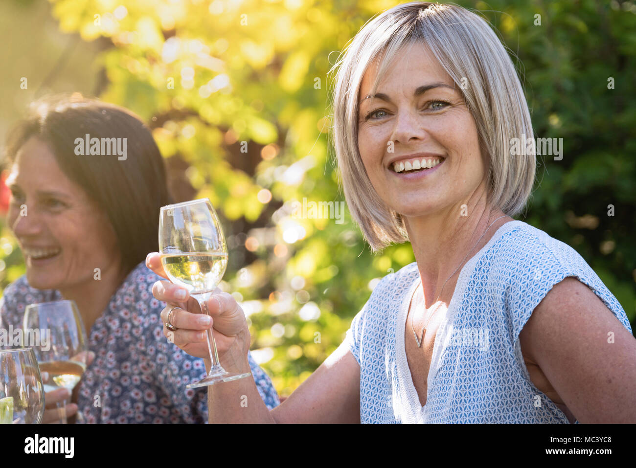 Group of friends gathered around a table in a garden to have a good time together. Focus on a beautiful woman looking at camera a drink at hand - Stock Image
