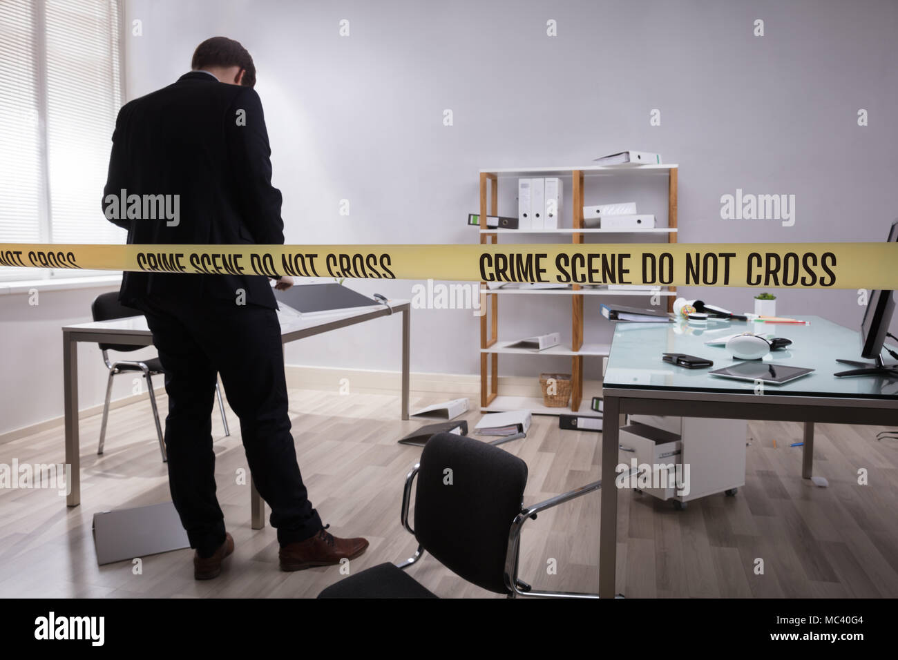 Investigator Collecting Evidence In Office Behind Yellow Crime Scene Tape - Stock Image