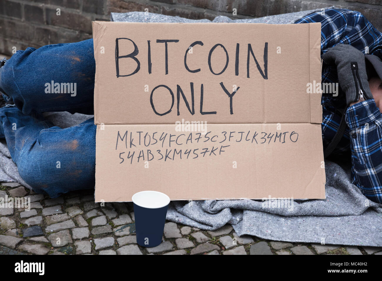 Beggar Sleeping On Street With Bitcoin Only Text On Cardboard Stock Photo
