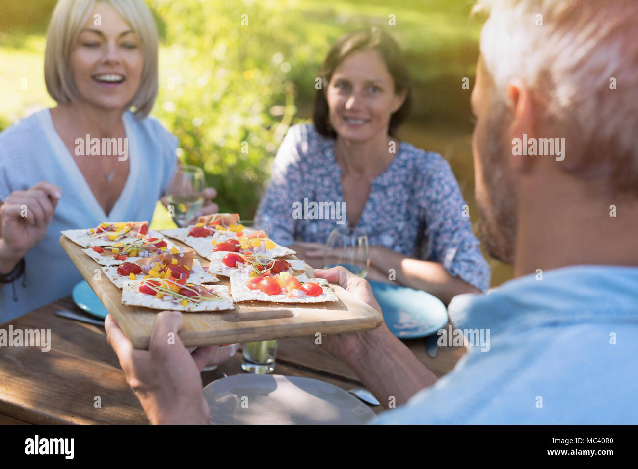 In summer. group of friends in their forties gathered around a table in the garden to share a meal. A man offers  hams toasts to guests - Stock Image