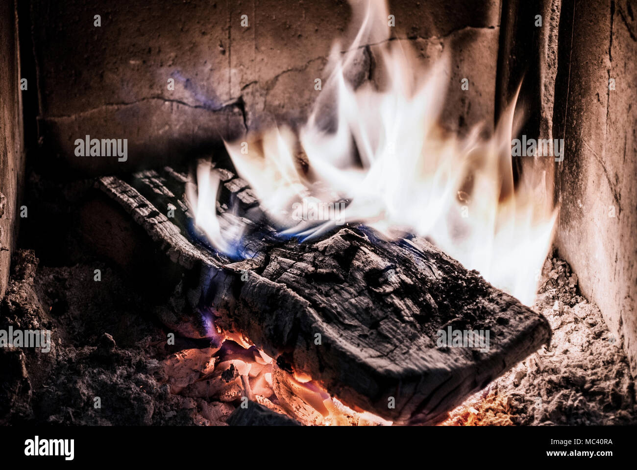 Wood in fire burning in old stove with ember. Close up - Stock Image