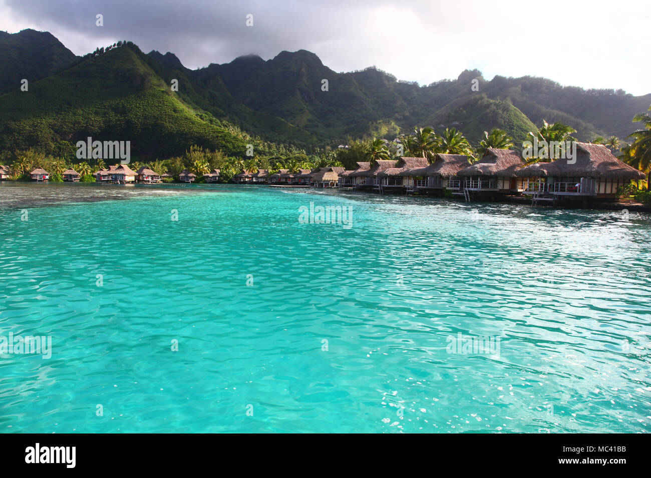 View towards the a bay in Moorea, with turquoise tropical water & bungalows over the sea. French Polynesia, South Pacific. - Stock Image