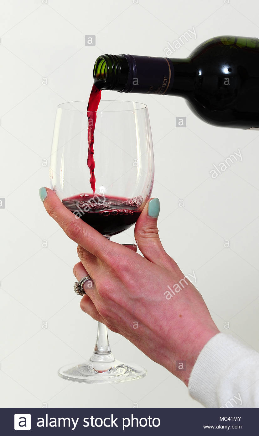 Undated file photo of a glass of red wine being poured. Drinkers who ignore UK alcohol consumption guidelines could be cutting years off their lives, according to new research. - Stock Image