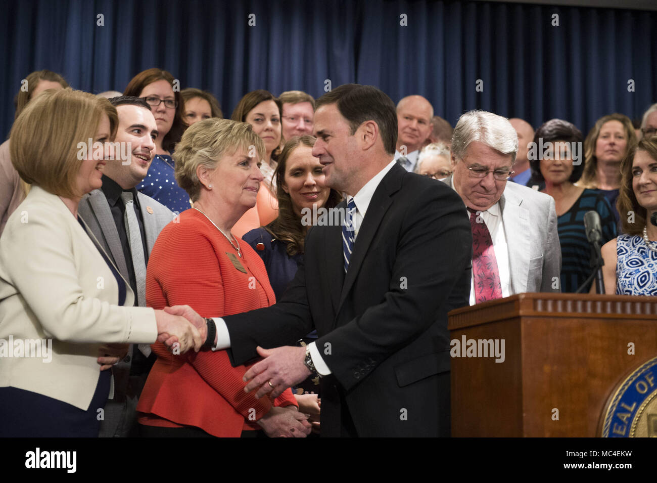 Phoenix, Arizona, USA. 12th Apr, 2018. Gov. DOUG DUCEY greets state legislators during a press conference on Thursday, at the state capitol in Phoenix, Arizona. After pressure and demonstrations by the advocacy group Arizona Educators United, Ducey announced a plan that would raise Arizona teacher salaries 20 percent by the 2020-21 school year. Credit: Ben Moffat/ZUMA Wire/Alamy Live News Stock Photo