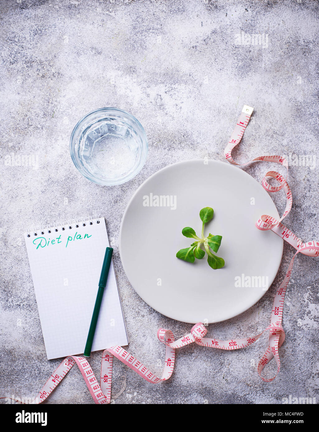 Plate with salad leaves, water and measuring tape - Stock Image