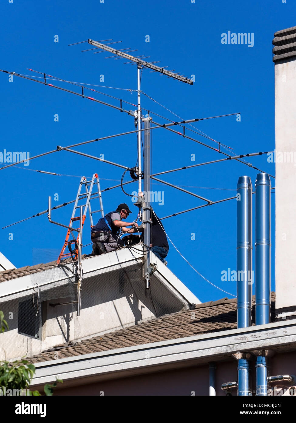 workers on the roof repair TV aerial - Stock Image