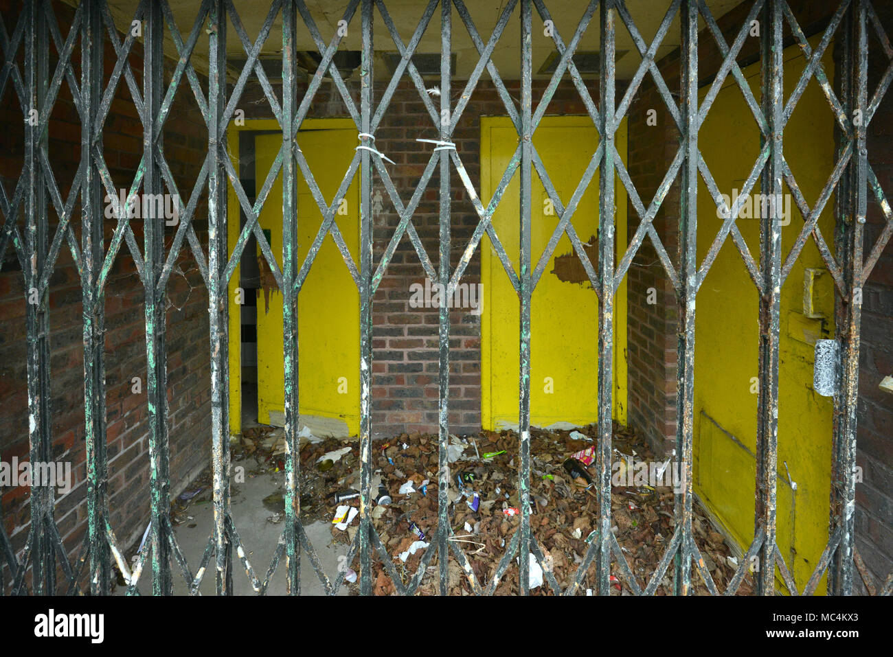 Vandalised yellow doors in a fenced off building, Newhaven, East Sussex. - Stock Image