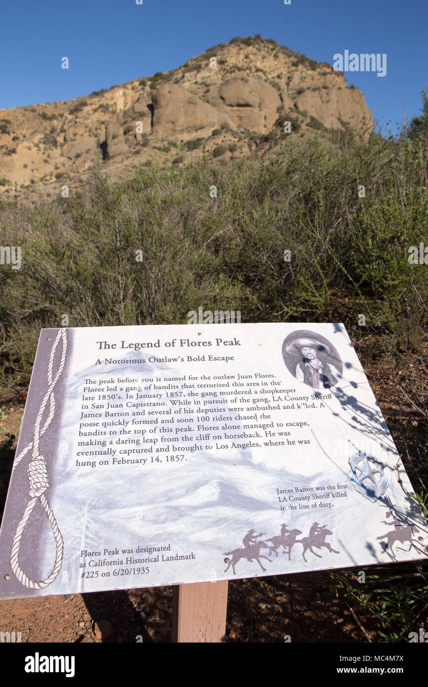 Information sign in Modjeska Canyon  Santa Ana Mountains of Orange County relating to the legend of outlaw Juan Flores. Flores Peak in the background - Stock Image