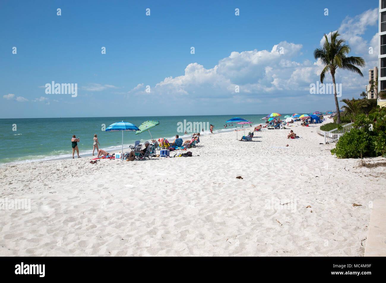 Vacationers in Naples, Florida enjoying beach activities. Sunbathing and having fun on the beach. Stock Photo